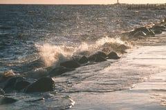 Wavebreaker in the sea - vintage effect. Wavebreaker in the sea with waves crushing over in sunset - vintage effect Royalty Free Stock Images