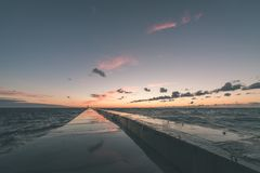 Wavebreaker in the sea - vintage effect. Wavebreaker in the sea with waves crushing over in sunset - vintage effect Stock Image