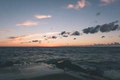 Wavebreaker in the sea - vintage effect. Wavebreaker in the sea with waves crushing over in sunset - vintage effect Stock Images