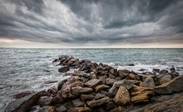 Artificial cliff made big stones. Waves of the Adriatic Sea crashing over an artificial cliff under stormy sky Royalty Free Stock Photos
