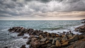 Artificial cliff made big stones. Waves of the Adriatic Sea crashing over an artificial cliff under stormy sky Royalty Free Stock Photography