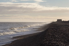 Waves on Aldeburgh beach with martello tower Royalty Free Stock Images