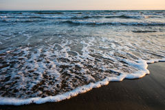 Waves approaching sandy beach during the sunset Stock Photo
