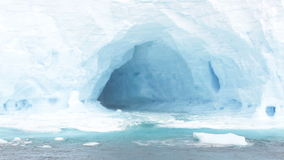 Waves in arches of iceberg stock footage