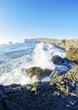 Waves crashing on rocky south coast of Iceland. Waves on Atlantic Ocean and rocky coast at Black beach and Dyrholaey natural arch in Vik along southern Iceland royalty free stock photo