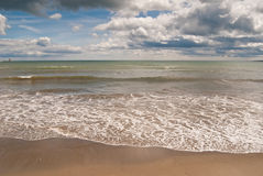 Waves on the beach. View of waves from the sea onto the beach in the foreground, with the horizon in the distance and clouds royalty free stock photography