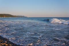 Waves on the beach against the backdrop of mountainous coast Stock Photo