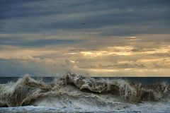 Waves on the beach with cloudy sky and plane royalty free stock photos