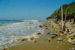 Waves, beach, fence, and hillside. Waves slide across the beach toward a crumbling fence and a green hillside in southern California Royalty Free Stock Image