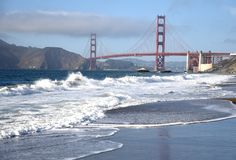 Waves on the beach with the golden gate. In the background stock photography