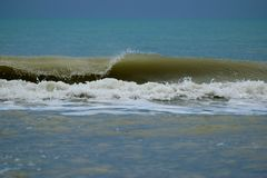 Waves on the beach in Lido di Jesolo. Waves breaking in the shallows of sandy beach in Lido di Jesolo, Italy, The water is green and the sky melts into green Stock Image