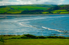 Waves. With beach and mountain and green fields clear blue sea Stock Photo