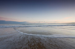 Waves on a beach at sunrise. Waves sweeping over beach at sunrise on Cornish beach Stock Photography