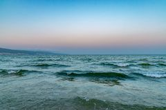 Waves at the beach at sunset in Sunny Beach on the Black Sea coast of Bulgaria. Bulgarian coastline copy space copyspace dawn day horizontal no people nobody royalty free stock image