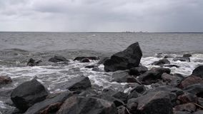 The waves beat against the rocks on the sea shore creating splashes stock video footage