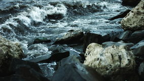 Waves beat against the rocks on the shore stock footage