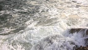 Waves beat against the stony shore of the sea form the spray and the foam. Slow motion. Large waves beat against the stony shore of the sea forming the many stock footage