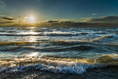 Waves, beautiful sunset, gold sunlight through blue turquoise water. Gold beautiful sunset light reflecting on turquoise waves of Lake Huron, Pinery Provincial Royalty Free Stock Images