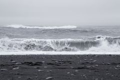 Waves in the beautiful volcanic black sand beach. Royalty Free Stock Photos