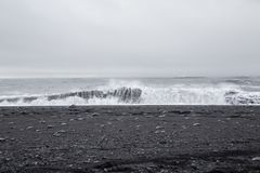 Waves in the beautiful volcanic black sand beach. Stock Images