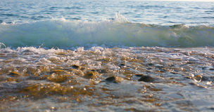 Waves. Beautiful wave rolls ashoreю Сolored stones royalty free stock photography