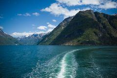Waves behind a cruise ship on a magnificent fjord in Norway. Sunny day . Emerald waters of the fjord. Mountains and sky with stock photos