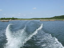 Waves behind motorboat. Driving with a motorboat on a lake stock images