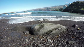 Waves on black sand beach with rocks in Tenerife, Canary islands, Spain, time lapse 4K. Landscape with waves on black sand beach with rocks and hotel buildings stock footage