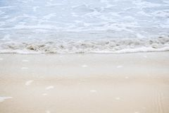 Waves blowing sand at the beach in the daytime. Royalty Free Stock Images