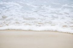 Waves blowing sand at the beach in the daytime. Stock Photography