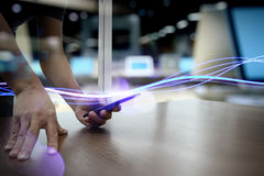 Waves of blue light and businessman using on smartphone royalty free stock photography