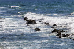 Waves and Blue Ocean Washing Over Rocks Royalty Free Stock Photography