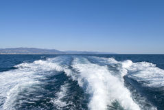 Waves on blue sea behind the boat Royalty Free Stock Photo