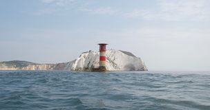 The Needles Lighthouse, Isle of Wight, with chalk cliffs and waves on the blue sea stock images