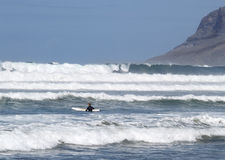 In the waves with a board. Man with white board before ride Royalty Free Stock Photography