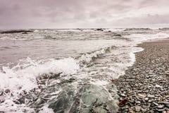 Waves break against the rocky coastline in Newport, Rhode Island. Under a stormy sky Stock Photo