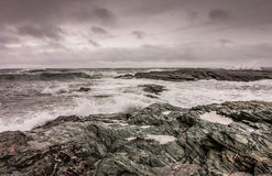 Waves break against the rocky coastline in Newport, Rhode Island. Under a stormy sky Royalty Free Stock Image