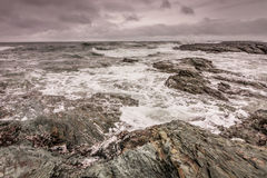 Waves break against the rocky coastline in Newport, Rhode Island. Under a stormy sky Stock Photos