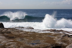 Waves break along rocky shore. On windy day Stock Photo