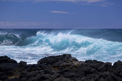 Waves break on black volcanic rocks Stock Photos