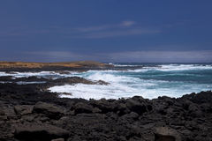 Waves break on black volcanic rocks Royalty Free Stock Image