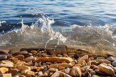 The waves break on the mini rocks. The waves break on the rocks stock photos