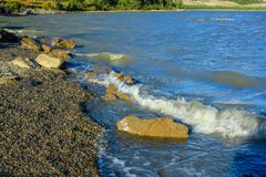 Scenes from the lakeshore, Lac de Arc, Alberta, Canada. Waves break on the rocks on the shore line as the winds pick up over the lake Royalty Free Stock Photo