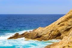 Waves break on rocky shore. Bali, Crete. Waves break on rocky shore. Raging sea an elemental power in a storm. Clear day at sea coast. Tourist beach resort in Stock Image