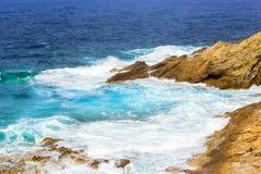 Waves break on rocky shore. Bali, Crete. Waves break on rocky shore. Raging sea an elemental power in a storm. Clear day at sea coast. Tourist beach resort in Royalty Free Stock Photos