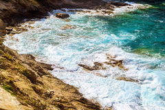 Waves break on rocky shore. Bali, Crete. Waves break on rocky shore. Raging sea an elemental power in a storm. Clear day at sea coast. Tourist beach resort in Royalty Free Stock Images