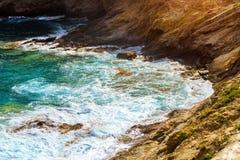 Waves break on rocky shore. Bali, Crete. Waves break on rocky shore. Raging sea an elemental power in a storm. Clear day at sea coast. Tourist beach resort in Stock Photo