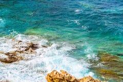 Waves break on rocky shore. Bali, Crete. Waves break on rocky shore. Raging sea an elemental power in a storm. Clear day at sea coast. Tourist beach resort in Stock Images