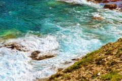 Waves break on rocky shore. Bali, Crete Stock Photo