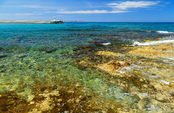 Waves break on rocky shore. Coast and beach resort village. Clear day at sea. Crete island, Greece, Beach Caves Stock Images